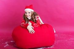 La muchacha está mintiendo en bolso rojo grande de la Navidad Fotos de archivo