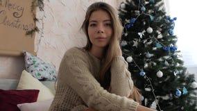 La muchacha está mintiendo en la cama en el fondo del árbol de navidad Año Nuevo almacen de video