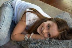 La muchacha está mintiendo en el piso Foto de archivo libre de regalías