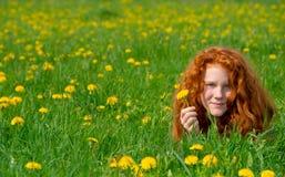 La muchacha está mintiendo en el prado de la primavera Imagen de archivo libre de regalías