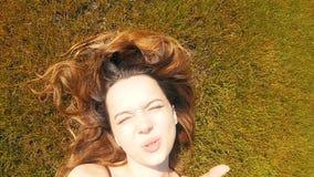 La muchacha está mintiendo en la hierba, agitando hola de la ciudad soleada, descansando, mirando la cámara, sonriendo Descanse,  almacen de metraje de vídeo