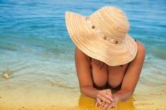 La muchacha está mintiendo en la playa. Imagenes de archivo