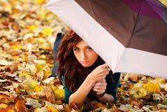 La muchacha está mintiendo en las hojas de otoño con el paraguas Imágenes de archivo libres de regalías