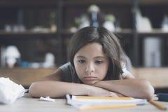 La muchacha está mintiendo en la tabla, su cabeza que descansa sobre los brazos cruzados y que mira indiferente a continuación Foto de archivo
