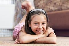 La muchacha está mintiendo la alfombra Fotografía de archivo libre de regalías