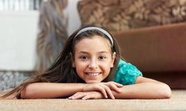 La muchacha está mintiendo la alfombra Fotos de archivo libres de regalías