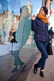 La muchacha está mirando la ventana de la tienda Foto de archivo