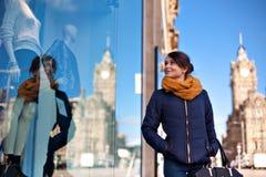 La muchacha está mirando la ventana de la tienda Fotografía de archivo