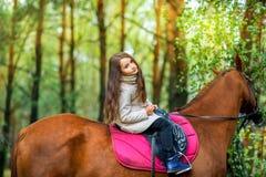 La muchacha está montando un caballo Foto de archivo libre de regalías