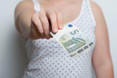 La muchacha está pagando con un billete de banco a estrenar del euro cinco Foto de archivo libre de regalías