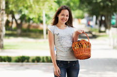La muchacha está permaneciendo en la calle con la cesta Foto de archivo libre de regalías