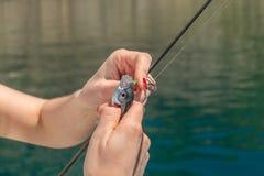 La muchacha está pescando en la bahía del mar Fotos de archivo libres de regalías