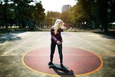 La muchacha está practicando el monopatín en un parque Imagenes de archivo
