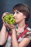 La muchacha está queriendo las uvas verdes Foto de archivo