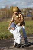La muchacha está recorriendo con su hermano Imagen de archivo libre de regalías