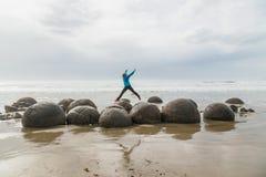 La muchacha está saltando entre los cantos rodados en la playa de Moeraki Nueva Zelanda fotografía de archivo