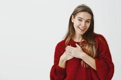 La muchacha está satisfecha con cumplidos del corowker en oficina Modelo femenino europeo encantador tocado en flojo rojo elegant foto de archivo