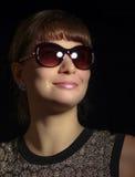 La muchacha está sonriendo y lleva las gafas de sol con la reflexión de destello Foto de archivo libre de regalías