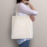 La muchacha está sosteniendo el bolso en blanco del eco del algodón, maqueta del diseño Fotos de archivo libres de regalías