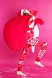 La muchacha está sosteniendo el bolso rojo grande de la Navidad Fotos de archivo libres de regalías