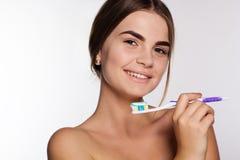La muchacha está sosteniendo el cepillo con crema dental aislado Foto de archivo libre de regalías