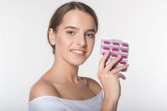 La muchacha está sosteniendo el tarro con las vitaminas Imágenes de archivo libres de regalías