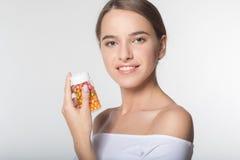 La muchacha está sosteniendo el tarro con las vitaminas Fotos de archivo