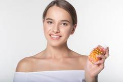 La muchacha está sosteniendo el tarro con las vitaminas Imagenes de archivo