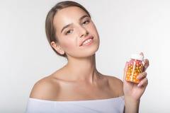 La muchacha está sosteniendo el tarro con las vitaminas Imagen de archivo