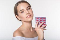 La muchacha está sosteniendo el tarro con las vitaminas Foto de archivo
