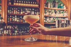 La muchacha está sosteniendo en su mano al vidrio de la bebida alcohólica fotografía de archivo