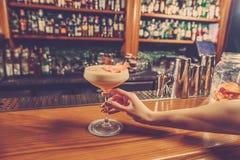 La muchacha está sosteniendo en su mano al vidrio de la bebida alcohólica imágenes de archivo libres de regalías