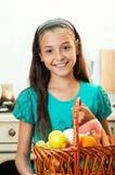 La muchacha está sosteniendo la cesta de alimento Imagenes de archivo
