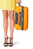 La muchacha está sosteniendo la maleta anaranjada Foto de archivo libre de regalías