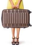 La muchacha está sosteniendo la maleta marrón Foto de archivo libre de regalías