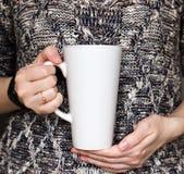 La muchacha está sosteniendo la taza blanca del Latte en manos El regalo de la mujer Maqueta para los diseños Imagen de archivo