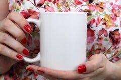 La muchacha está sosteniendo la taza blanca en manos foto de archivo libre de regalías