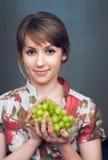 La muchacha está sosteniendo las uvas frescas Fotos de archivo