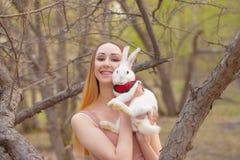 La muchacha est? sosteniendo un conejo blanco Mujer hermosa con una liebre imagenes de archivo