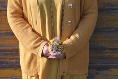La muchacha está sosteniendo un pequeño ramo de la flor Imagenes de archivo
