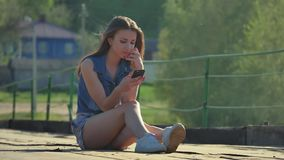 La muchacha está sosteniendo un smartphone La muchacha de Internet en medios sociales del smartphone se sienta en el puente del h metrajes
