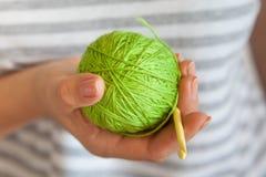 La muchacha está sosteniendo una bola del hilado de lana verde claro Fotos de archivo