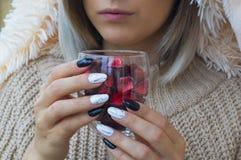 La muchacha está sosteniendo una copa de vino con el relleno decorativo fotografía de archivo