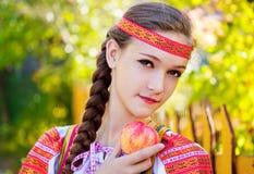 La muchacha está sosteniendo una manzana Imagenes de archivo