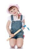 La muchacha está sosteniendo una pala del jardín Imagenes de archivo