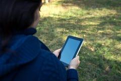 La muchacha está sosteniendo una tableta Foto de archivo