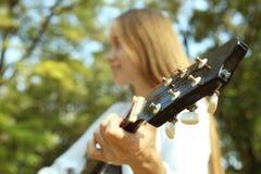 La muchacha está tocando la guitarra Imágenes de archivo libres de regalías