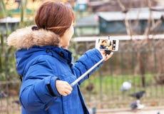 La muchacha está tomando el selfie (foto) con el smartphone y el monopod (el palillo) Fotografía de archivo