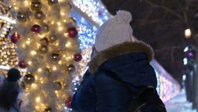 La muchacha está tomando imágenes de las decoraciones del día de fiesta Iluminación de tarde almacen de video