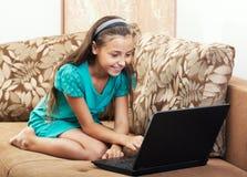 La muchacha está trabajando en la computadora portátil Foto de archivo